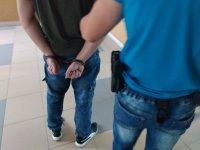 mężczyzna w kajdankach oraz policjant
