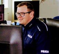 Policjant - dyżurny siedzący na stanowisku kierowania przed monitorem.