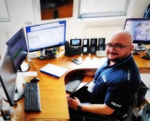 Policjant dyżurny na stanowisku kierowania jednostką, przed nim monitory komputerów.