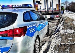 Radiowóz, samochód ciężarowy i policjant.