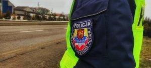 Napis na mundurze Komenda Powiatowa Policji w Grajewie, w tle zabudowania, policjant ruchu drogowego
