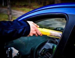 policjant bada stan trzeźwości kierowcy, ręka policjanta z urządzeniem do badania stanu trzeźwości